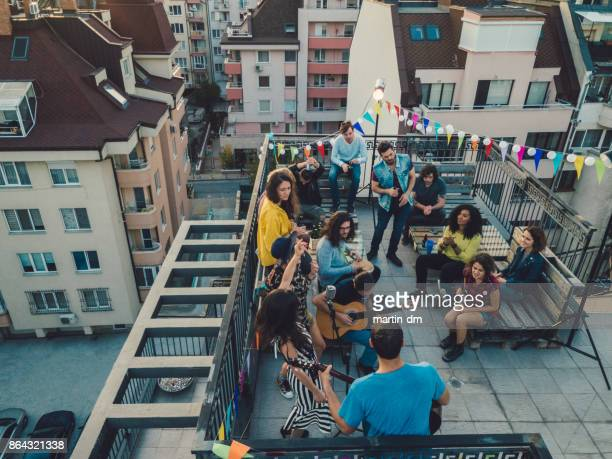 friends enjoying a rooftop concert - martin guitar stock photos and pictures
