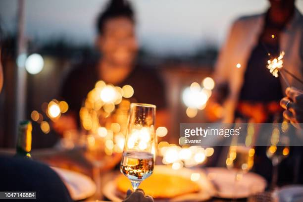 friends enjoying a rooftop party with champagne and sparklers - incidental people stock pictures, royalty-free photos & images