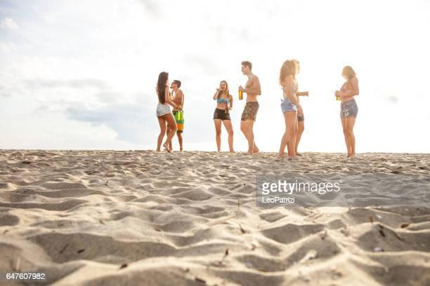 Amigos disfrutando y divirtiéndose a vacaciones en la playa