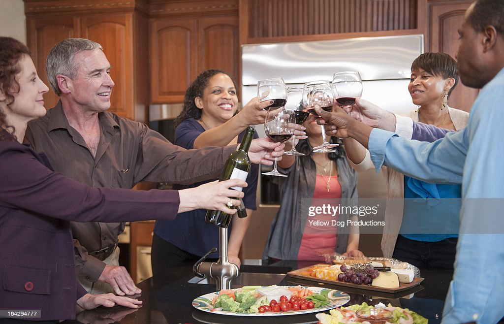 Friends enjoying and toasting drinks at a party : Stock Photo