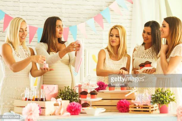 Friends enjoying baby shower party food and drinks