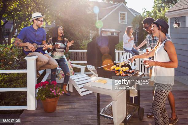 friends enjoying barbecue on patio - barbecue social gathering stock pictures, royalty-free photos & images