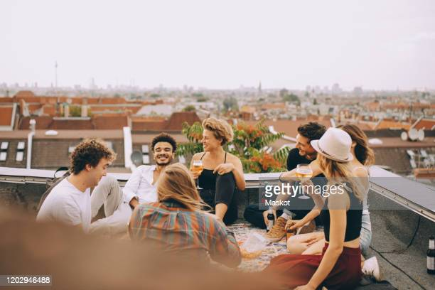 friends enjoying beer while sitting together on terrace at rooftop party - generation y stock-fotos und bilder
