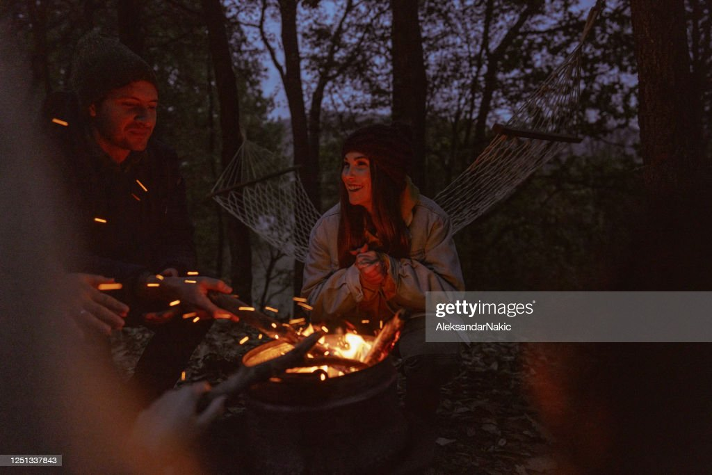 Friends enjoying by the campfire : Stock Photo