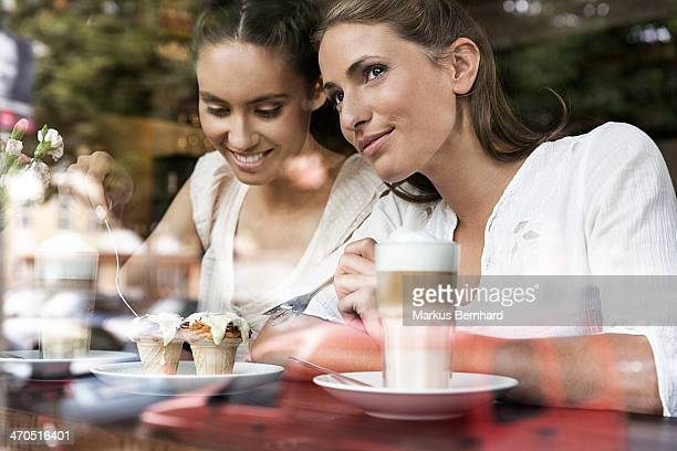 Friends enjoying cake in cafe.