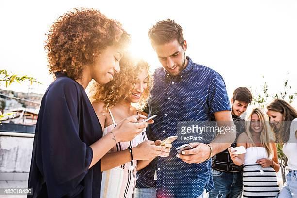 Friends enjoying city life using mobile phone