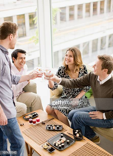 Friends enjoying cocktails and sushi at party