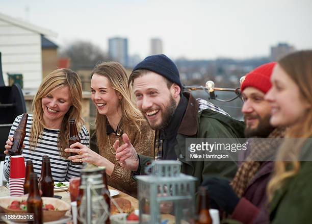 Friends enjoying company at table in roof garden.