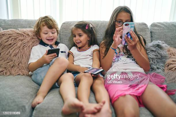friends enjoying computer games on sofa - three people stock pictures, royalty-free photos & images