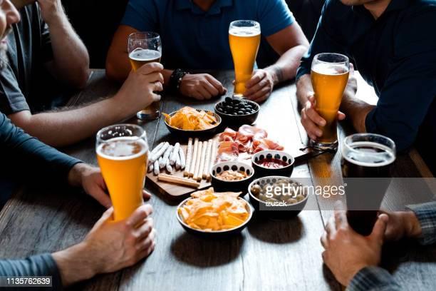 amici che si godono la birra artigianale a tavola al pub - izusek foto e immagini stock