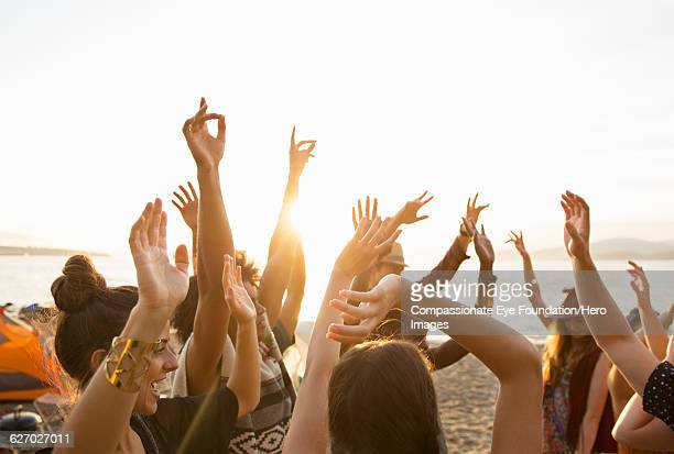 friends enjoying dancing on beach - arms raised stock pictures, royalty-free photos & images