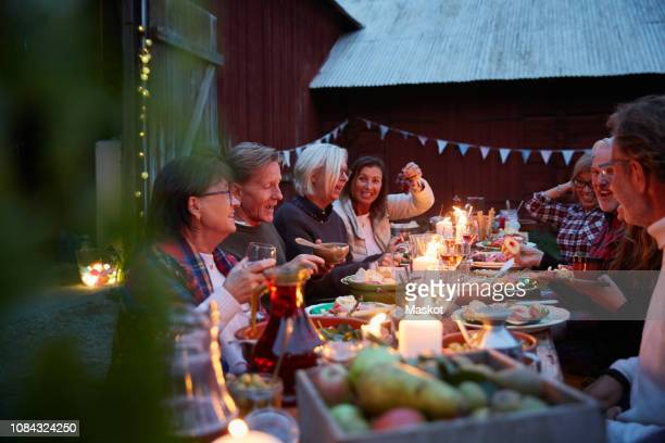 friends enjoying dinner party outside barn at farm - farmhouse stock pictures, royalty-free photos & images