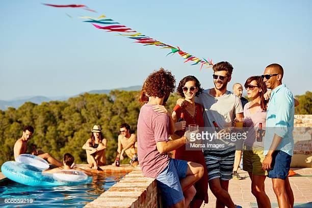 friends enjoying drinks at poolside - bebida fotografías e imágenes de stock