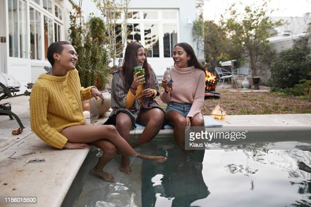 friends enjoying drinks while sitting at poolside - adults only stock pictures, royalty-free photos & images