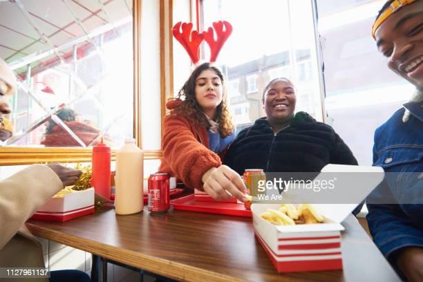friends enjoying festive fried chicken in cafe - schnellimbiss stock-fotos und bilder
