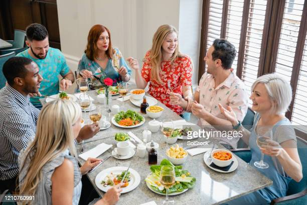 friends enjoying food and wine at restaurant - honour stock pictures, royalty-free photos & images