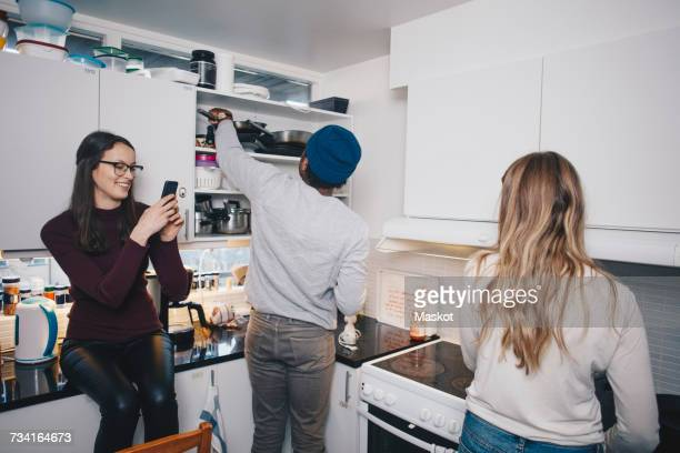 Friends enjoying in kitchen at college dorm