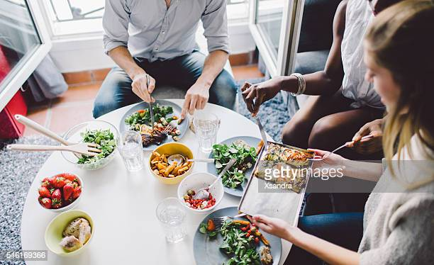 friends enjoying lunch at home - man eating woman out stock photos and pictures