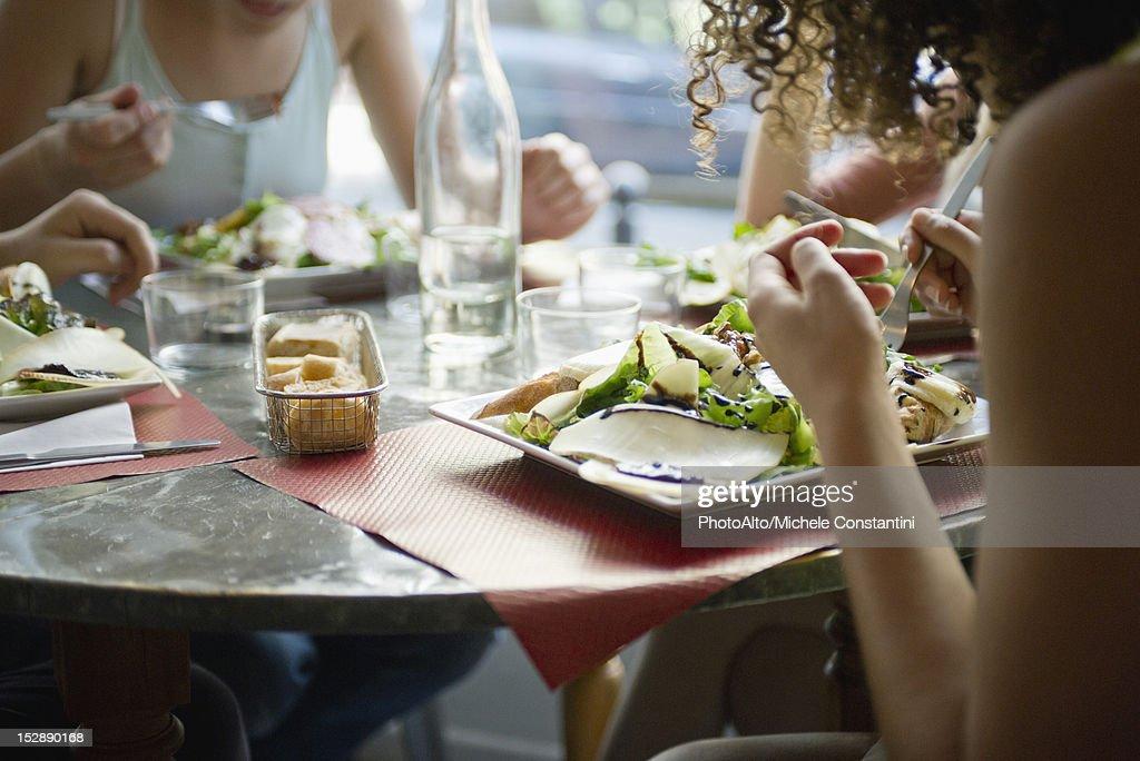 Friends enjoying meal in cafe, cropped : Foto de stock