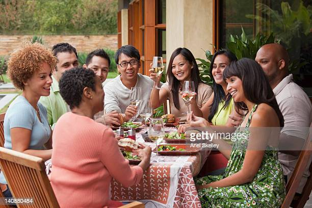 friends enjoying meal together outdoors - middelgrote groep mensen stockfoto's en -beelden
