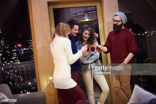 friends enjoying mulled wine in chalet - handen in de zakken stockfoto's en -beelden