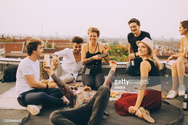 friends enjoying music on speaker during rooftop party at terrace against sky - day stock pictures, royalty-free photos & images