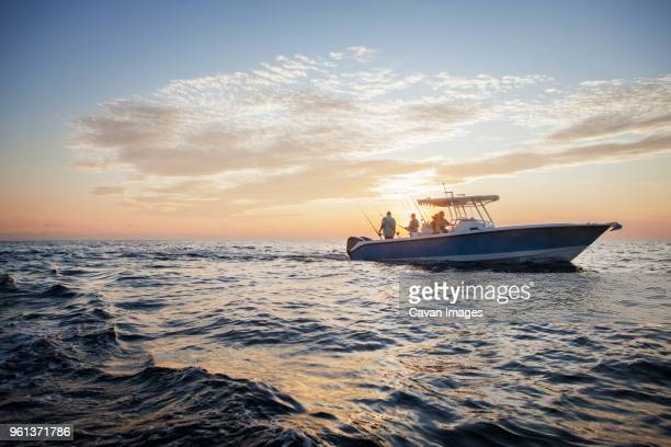 friends enjoying on boat at sea against sky during sunset - fishing boat stock pictures, royalty-free photos & images
