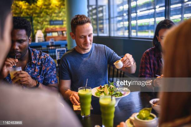 friends enjoying paleo food and drink at vertical farm cafe - close to stock pictures, royalty-free photos & images