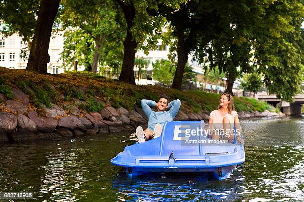 Friends enjoying pedal boating on river in city