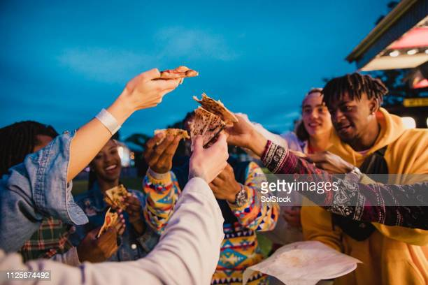 Friends Enjoying Pizza at Festival