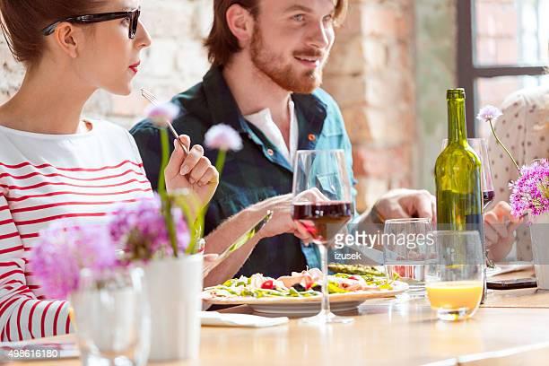 freunde genießen sie pizza im restaurant - izusek stock-fotos und bilder