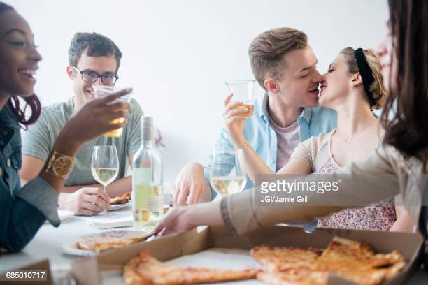Friends enjoying pizza, wine and beer