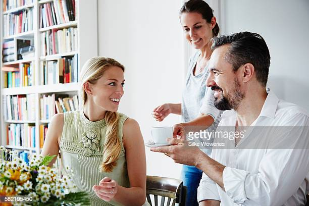 friends enjoying teatime eating raspberry cake at home