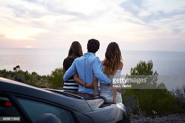 3 Friends enjoying the view of the sunset over sea