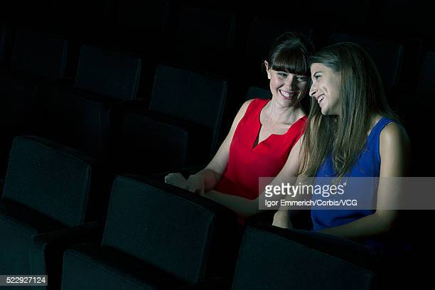 friends enjoying themselves at cinema - corbis images stock photos and pictures