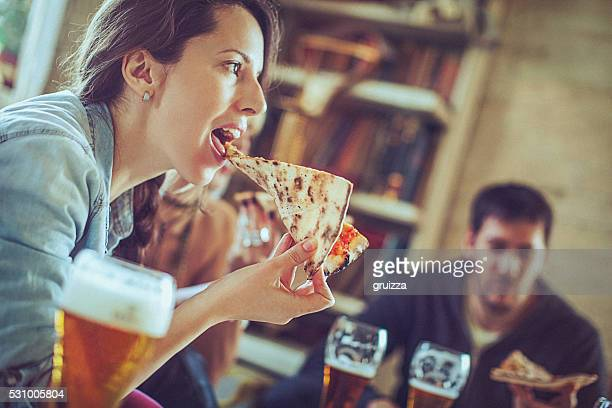 Friends enjoying time eating pizza and drinking beer together