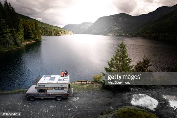 friends enjoying view of lake on top of campervan, cathedral grove, british columbia, canada - grove_(nature) stock pictures, royalty-free photos & images