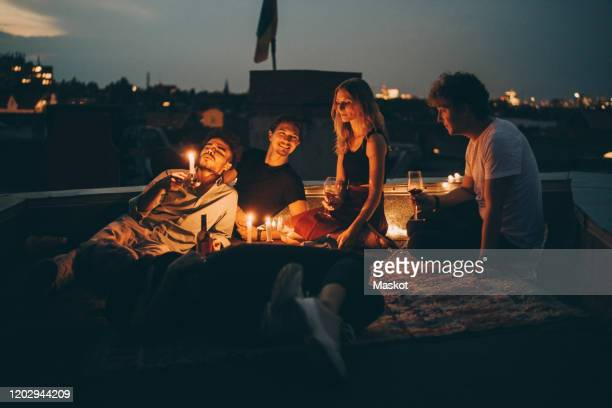 friends enjoying wine in candlelight while relaxing on terrace at city during dusk - roof stock pictures, royalty-free photos & images
