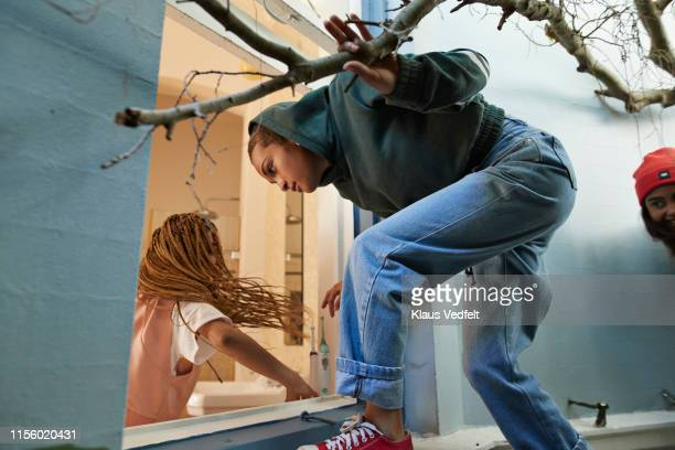 friends entering house through window - falsenews stock pictures, royalty-free photos & images