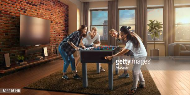 Friends enthusiastically play table football/kicker game