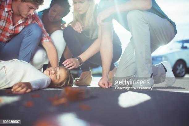Friends examining injured girl on sidewalk