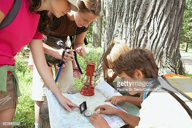 Friends examining map in woods