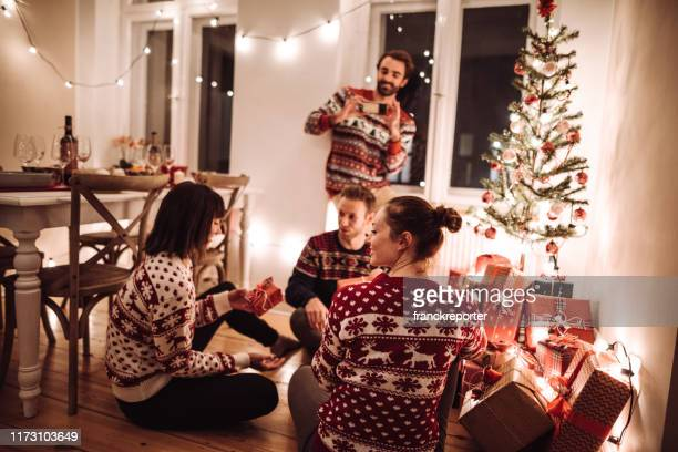 friends exchanging christmas present at home - exchanging stock pictures, royalty-free photos & images