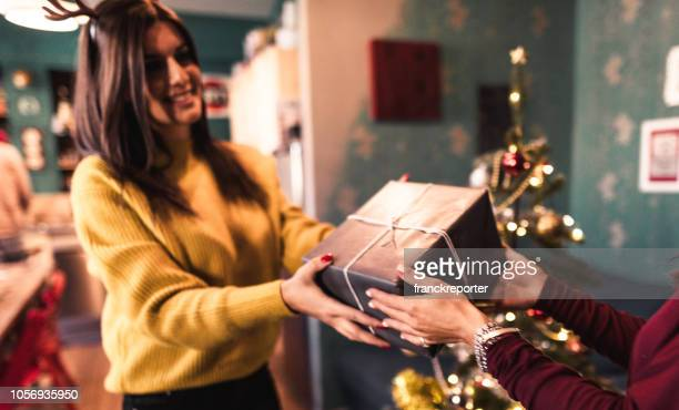 friends exchanging christmas presents - receiving stock pictures, royalty-free photos & images