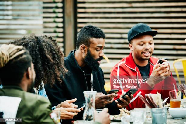 Friends exchanging contact information on smart phones during party at outdoor bar