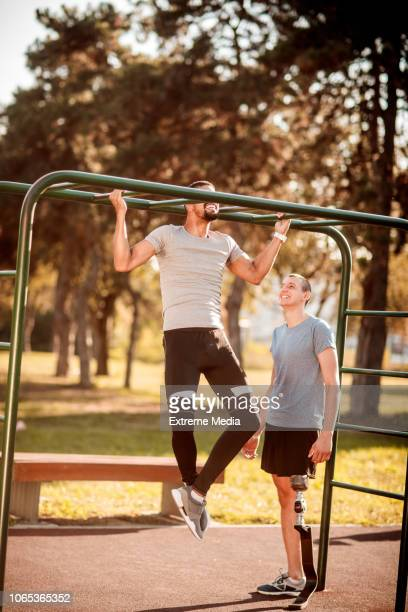 Friends exercising chin-ups in the outdoor gym