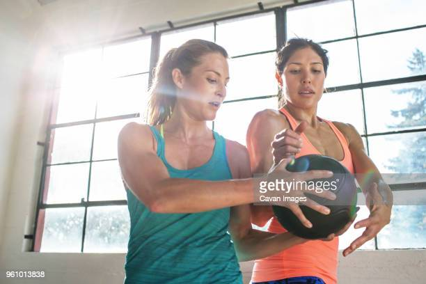 friends exercising with medicine ball by window in gym - medicine ball stock pictures, royalty-free photos & images