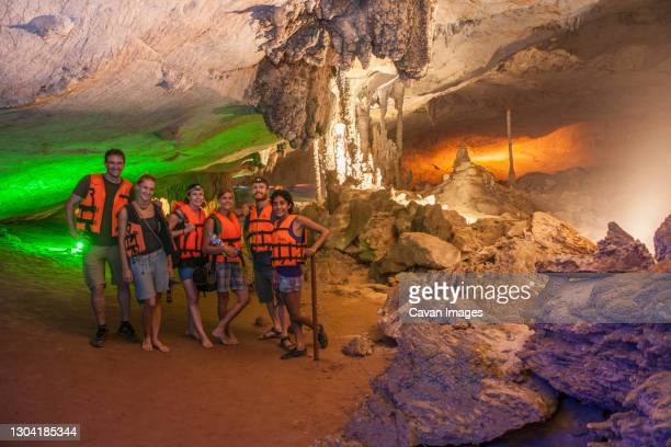 friends exploring the illuminated kong lo cave in laos - speleology stock pictures, royalty-free photos & images