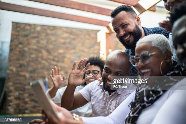 vrienden / familie die een videopraatje doet gebruikend een digitale tablet thuis - zwaaien gebaren stockfoto's en -beelden
