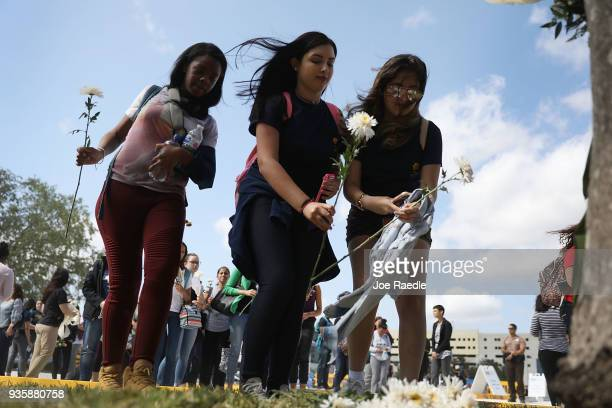 Friends family Florida International faculty and students lay flowers at a makeshift memorial as they mourn together during a vigil for victims of...